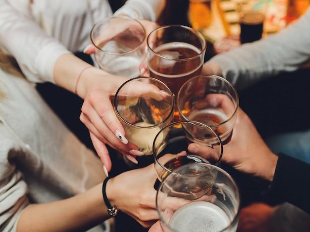 Sluit omhoog geschoten van groep mensen rammelende glazen met wijn of champagne
