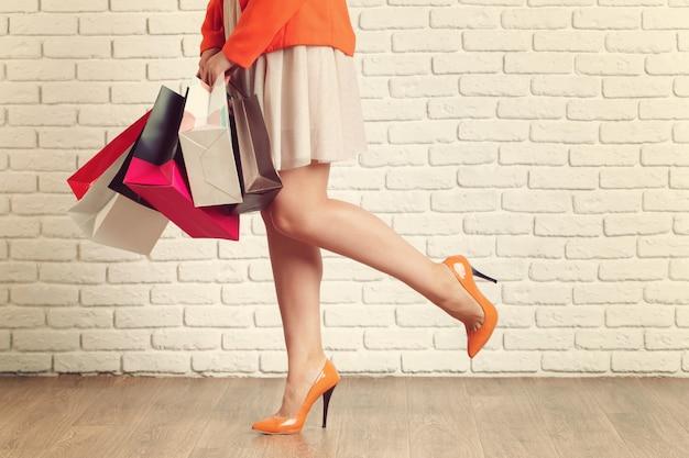Sluit omhoog geschoten van jong vrouwenbeen dragende kleurrijke het winkelen zakken