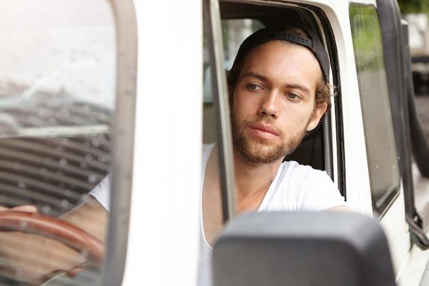 Sluit omhoog geschoten van modieuze jonge ongeschoren mens die glb achteruit draagt, binnen zijn jeep zit en weg bekijkt terwijl het parkeren van zijn auto met vierwielaandrijving