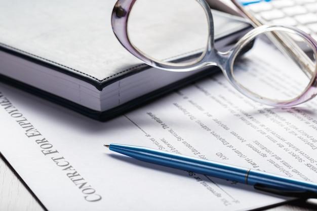 Sluit omhoog geschoten van oogglazen op de documenten van het contractdocument bedrijfsconcept