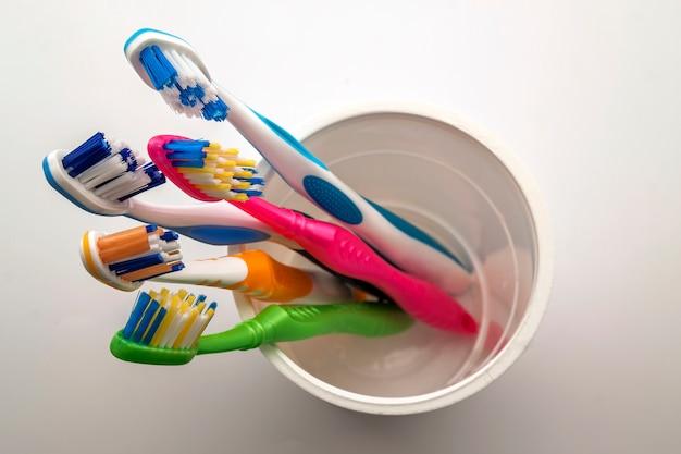 Sluit omhoog geschoten van reeks multicolored tandenborstels in glas op schoon toilet op witte tandachtergrond ,.