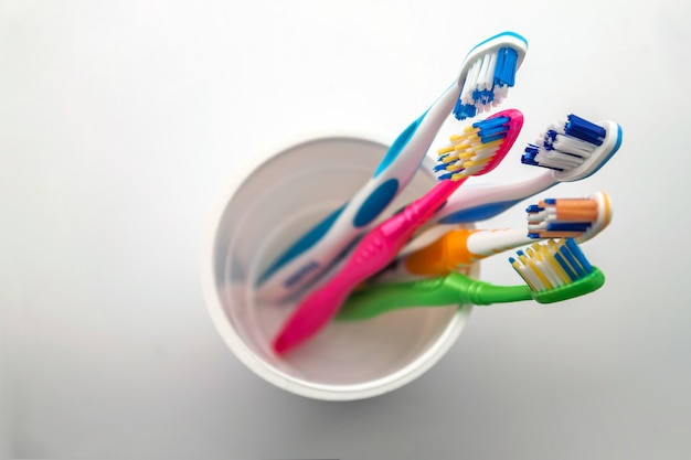 Sluit omhoog geschoten van reeks multicolored tandenborstels in glas op schoon toilet, tandconcept.