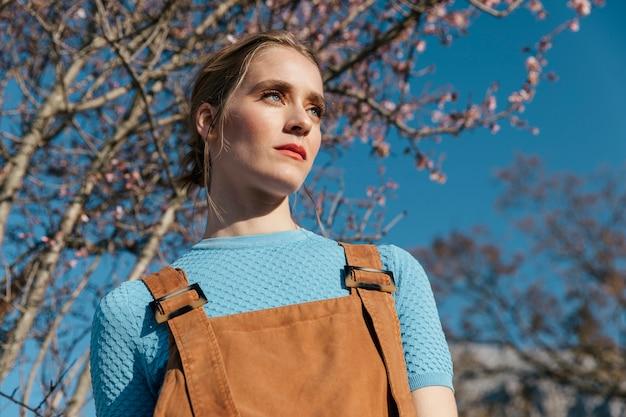 Sluit omhoog geschoten vrouwelijk model onder bloeiende boom