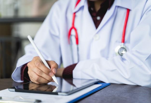 Sluit omhoog geschotene hand van artsen met stethoscoop gebruiken tabletten om behandelingsrapporten te schrijven of te bekijken