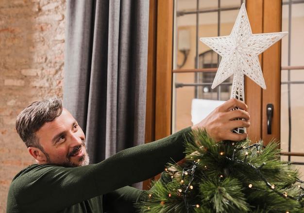 Sluit omhoog geschotene oudere mens die de ster op de boom zetten