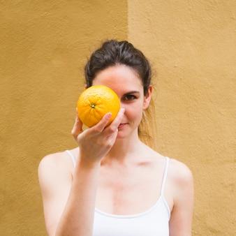 Sluit omhoog geschotene vrouw behandelend gezicht met sinaasappel