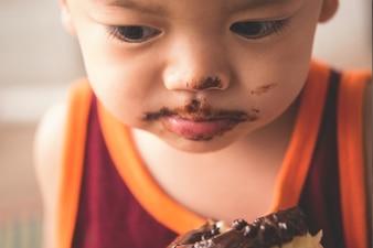 Sluit omhoog gezicht van hongerige kleine jongen eaitng hete doughnut