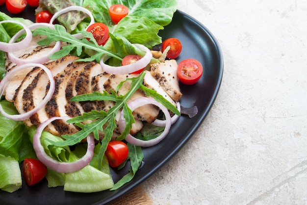 Sluit omhoog gezonde salade met geroosterde kip, uien en tomaten. gezond eten.