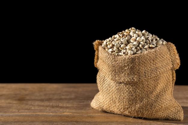 Sluit omhoog gierstrijst of gierstkorrels in kleine zak op houten lijst