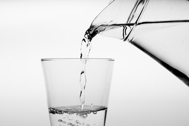 Sluit omhoog gietend drinkwater in glas