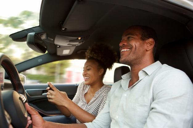 Sluit omhoog glimlachende afrikaanse amerikaanse man en vrouw in auto het glimlachen