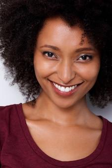Sluit omhoog glimlachende jonge afrikaanse amerikaanse vrouw met krullend haar