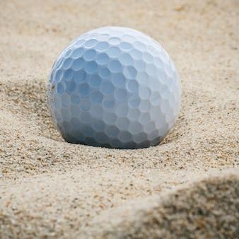Sluit omhoog golfbal in de ondiepe diepte van de zandbunker van gebied.