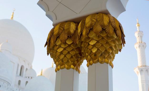 Sluit omhoog gouden decoratie van kolommen in grote witte moskee in abu dhabi