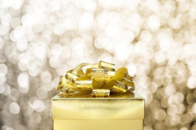 Sluit omhoog gouden huidige doos met grote boog bij achtergrond van het bokeh de witte onduidelijke beeld