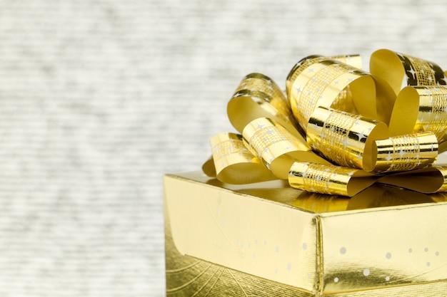 Sluit omhoog gouden huidige doos met grote boog bij bokeh