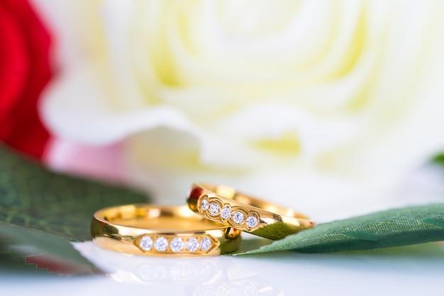 Sluit omhoog gouden ring en rode rozen op wit