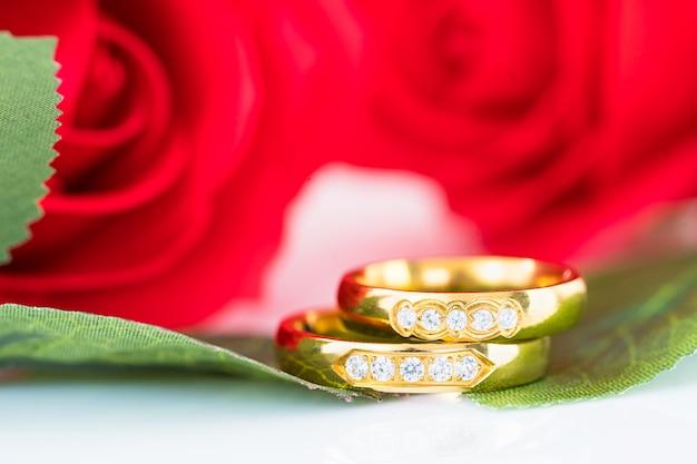 Sluit omhoog gouden ring en rode rozen