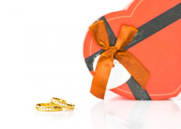 Sluit omhoog gouden ringen en hart-vormig op wit