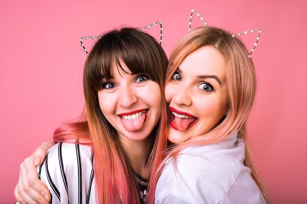Sluit omhoog grappig gek portret van gelukkige meisjes die pret hebben die tongen tonen en de oren van de partijkat, roze muur en jeugdstijl van haren, beste vriendenknuffels dragen.