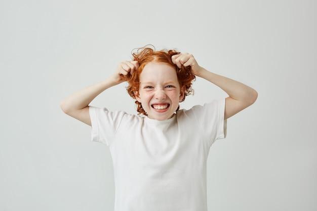 Sluit omhoog grappig portret van weinig jongen met gemberhaar en sproeten glimlachend met tanden, hebbend gelukkige uitdrukking, houdend haar met handen.