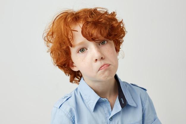 Sluit omhoog grappig portret van weinig jongen met rood krullend haar en sproeten kijkend met ongelukkige uitdrukking
