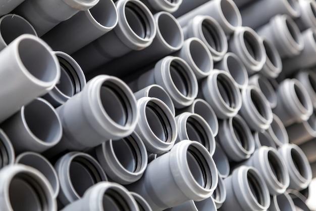 Sluit omhoog grijze loodgieterswerk plastic pijpen. kleurrijke grote plastic pijpen gebruikt op de bouwplaats.