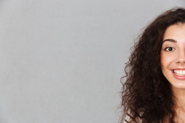 Sluit omhoog half gezichtsportret van aantrekkelijke krullende vrouw met ring in neus stellend glimlachend met perfecte witte tanden over grijze muur