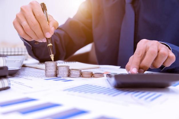 Sluit omhoog, hand die de stapel van geldmuntstukken in besparingsgeld zetten en bedrijfsconcept kweken.