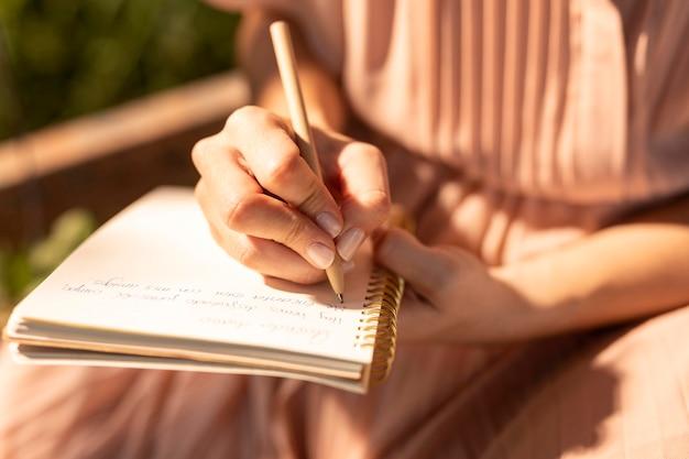 Sluit omhoog hand die op notitieboekje schrijft