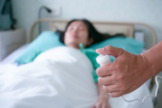 Sluit omhoog hand drukkend de hulpknop voor verpleegster die noodsituatie in het ziekenhuis roept