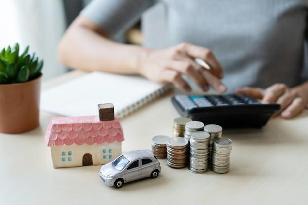 Sluit omhoog hand gebruikend calculator, stapel muntstukken, stuk speelgoed huis en auto op lijst, spaarend voor toekomst, leid aan succes, bedrijfs en financier concept.