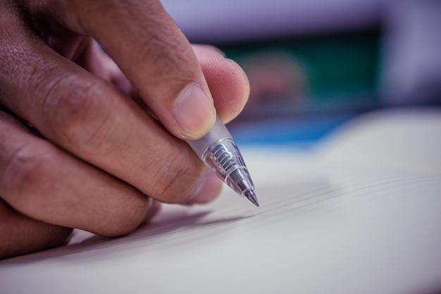 Sluit omhoog hand gebruikend pen schrijvend op notitieboekje