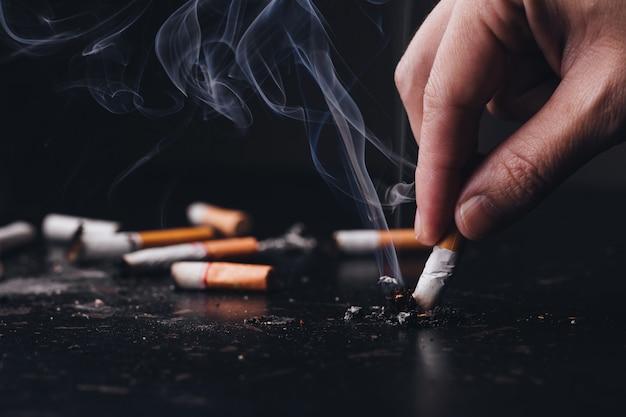 Sluit omhoog hand gehouden een sigaret om rook van het branden te verpletteren, houd op rokend. wereld geen tabaksdag