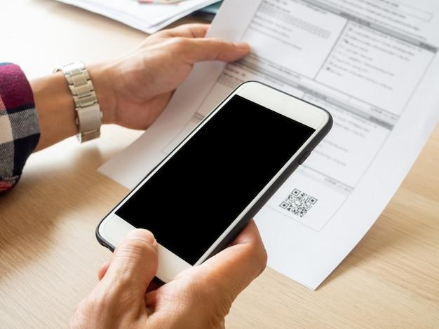 Sluit omhoog hand houdend slimme telefoon om qr-code van factuur op documenten te scannen.