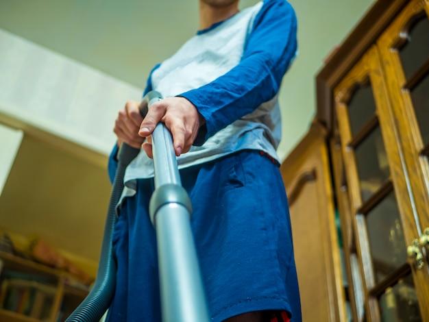 Sluit omhoog hand houdend stofzuiger op het tapijt in de ruimte