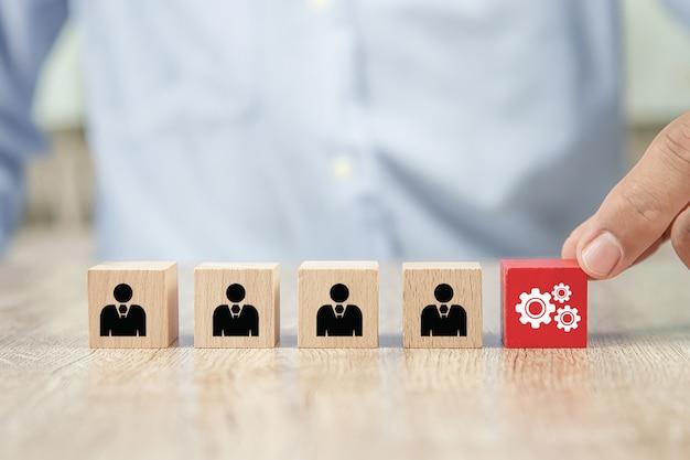 Sluit omhoog hand kies radertjepictogrammen op kubus houten stuk speelgoed blokken, conceptenpersoneel.