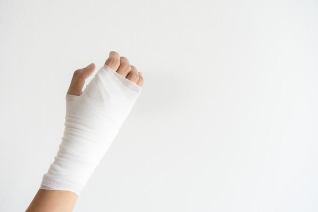 Sluit omhoog hand pijnlijk met verband op witte muur. hand van de zorg van de de verwondingsbreuk van vrouwen medisch door arts.