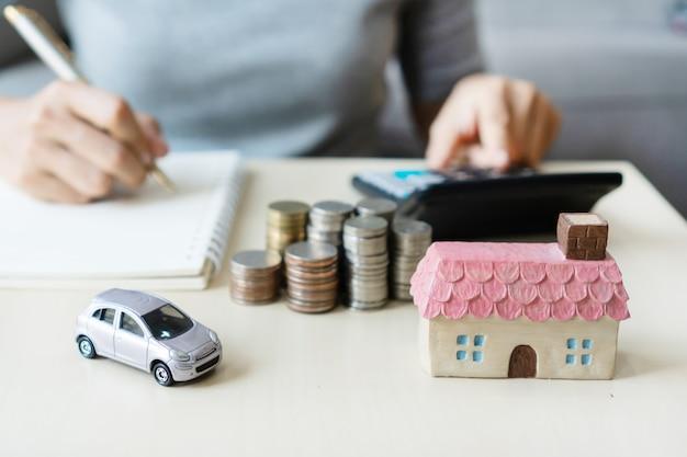 Sluit omhoog hand schrijvend terwijl het gebruiken van calculator, stapel muntstukken, stuk speelgoed huis en auto op lijst, die voor toekomst sparen, aan succes leiden, concept financieren.