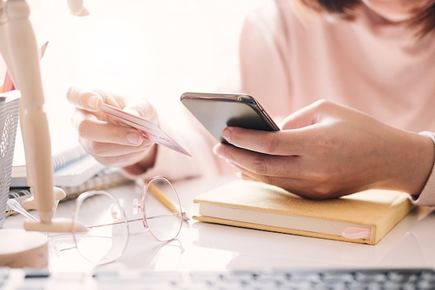 Sluit omhoog hand van de creditcard van de vrouwenholding en thuis het gebruiken van slimme telefoon. online winkelen concept.