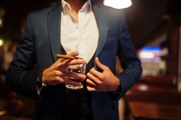 Sluit omhoog hand van de knappe goed-geklede arabische mens met glas whisky en sigaar die bij bar wordt gesteld.