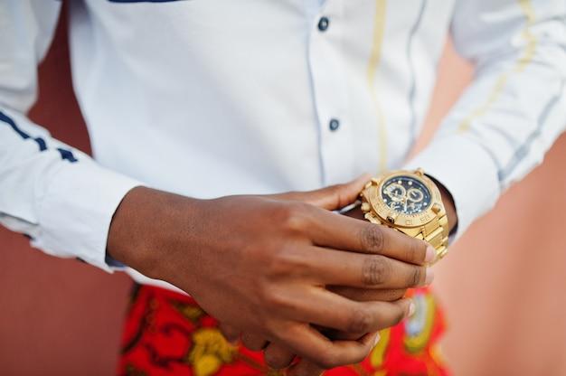 Sluit omhoog hand van de knappe modieuze afro-amerikaanse modelmens bekijken zijn luxe gouden horloges.