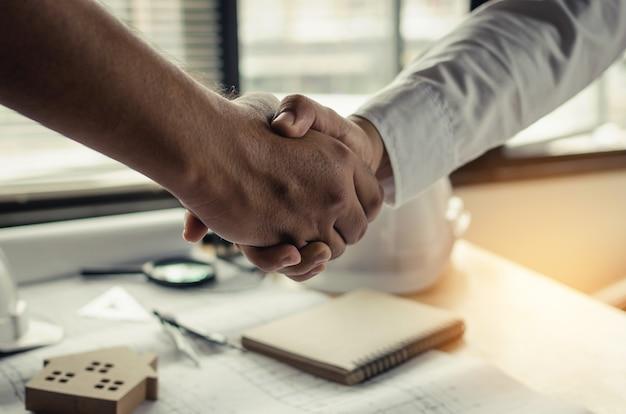 Sluit omhoog hand van de shake van de de contractantshand van het bouwvakkersteam