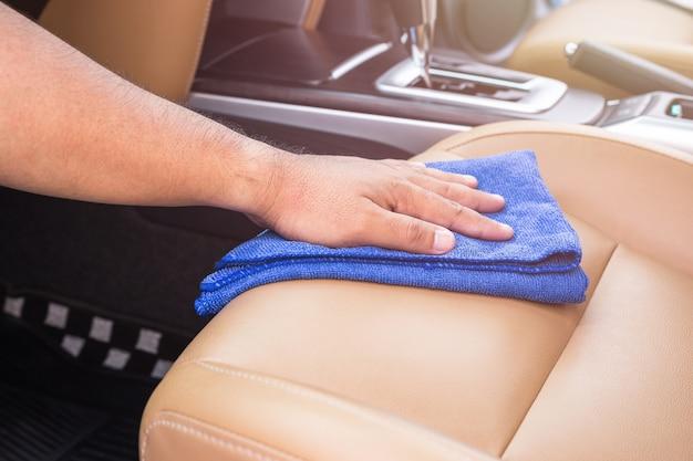 Sluit omhoog hand van mensen die blauwe microfiberdoek houden en binnen de suv-auto schoonmaken