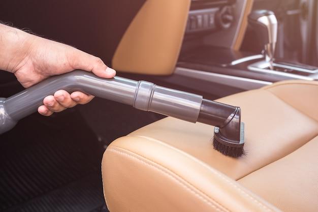 Sluit omhoog hand van mensen die stofzuiger houden en binnen de suv-auto schoonmaken