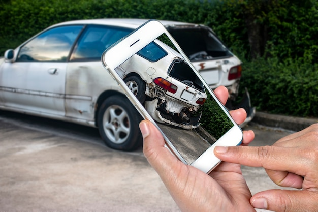 Sluit omhoog hand van smartphone van de mensenholding en neem foto van autoongeval