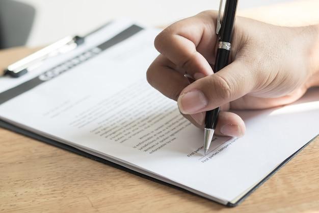 Sluit omhoog hand van zakenman ondertekenend contractdocument