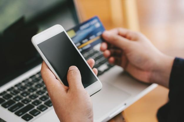 Sluit omhoog handen betaalbaar online. man handen die een creditcard houden en slimme telefoon voor online het winkelen gebruiken