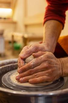 Sluit omhoog handen die aardewerk doen