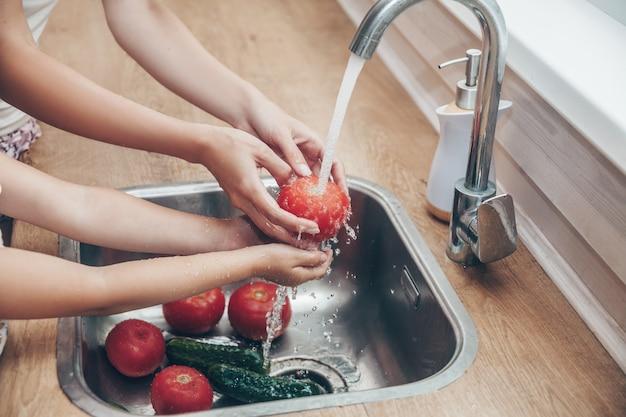 Sluit omhoog handen die groenten in keuken wassen